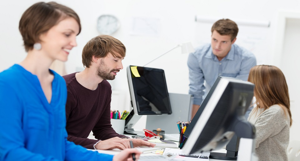 Smiling employees working at computers
